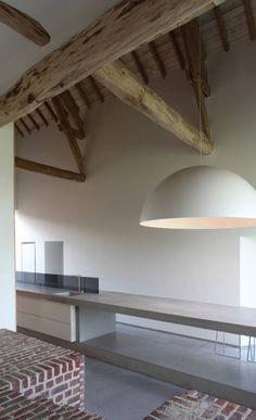 House DM / Lensass Architects - love the simplicity and calmness of this modern concrete kitchen slicing through this space and contrasting beautifully with the old roof timbers above