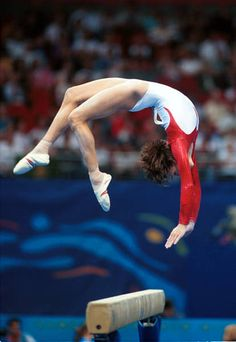Canadian gymnast Yvonne Tousek performing difficult back handspring move on balance beam.