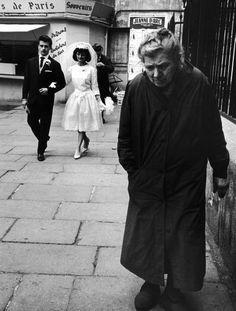 Elderly woman walking along street while bride and groom walk behind. Photograph by Alfred Eisenstaedt. Paris, June 1963.
