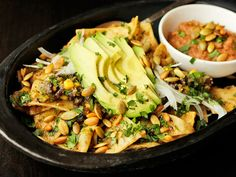 Chilaquiles with pepitas, charred corn, and black beans. A vegan Mexican dish.