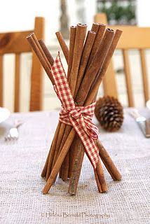 Simple table decoration made of cinnamon sticks with a red and white ribbon