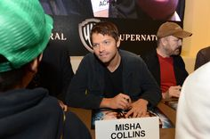 SUPERNATURAL star Misha Collins talks to a fan at the Warner Bros. booth at Comic-Con 2012 (© WBEI. All Rights Reserved.)