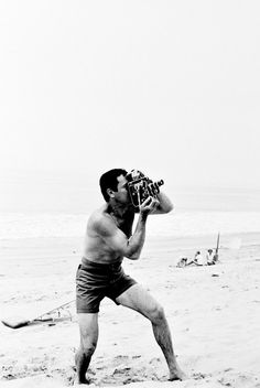 Tony Curtis on the beach with a camera, 1967.