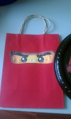 Ninjago Birthday Party Bags - Search google for Ninjago images.   There are many good ones available.   Bought goodie bags at the dollar store.  Printed out ninjago eyes and cut them out and the kids glued them on.   Ninjago party bags.