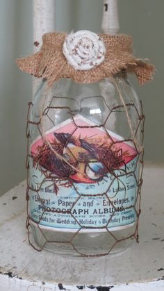 I added to the idea of chicken wire wrapped around a jar I saw on fourcornersdesign by putting on a label from Graphics Fairy and adding a burlap covered lid with a fabric flower.