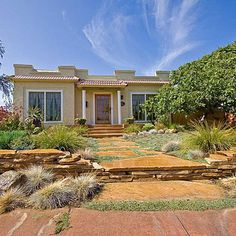 Drought-tolerant yard  A low retaining wall of stacked flagstone has the effect of setting this San Diego house and garden on a pedestal. The wide pathway, also of flagstone, adds importance, too.