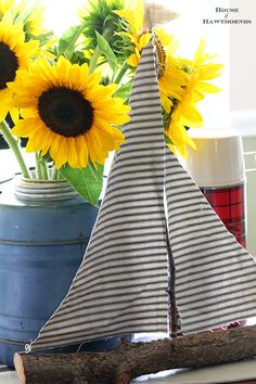 Happy little sunflower vignette using vintage picnic jug, thermoses and a twig sailboat