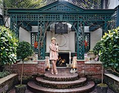 """charlotte moss - Charlotte Moss in her garden with metal pergola and limestone built-in benches. The fireplace is gas and can be turned on in any season. """"Putting in the pergola was an attempt to create privacy and shade,"""" says Moss. """"The placement of the fireplace lines up perfectly with the entrance-hall gallery in the house, so when you come in, the fire is going; it just pulls you out there."""""""
