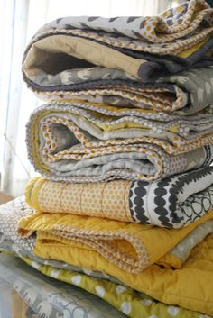 a pile of gray and yellow crib quilts