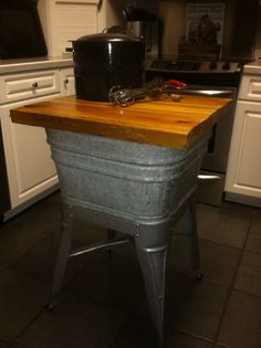 Old galvanized wash tub turned repurposed into kitchen island. I've used mine as a microwave stand in my country kitchen.