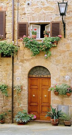 wood door, the stone wall ... the lantern light fixture ... the small shuttered window with flowerbox ... the warm colors ... ahhhhh