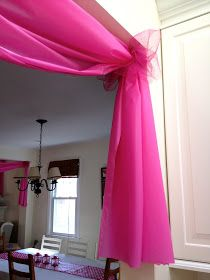 Use $1 plastic tablecloths to decorate doorways and windows for parties, etc.. Wonderful idea! Just think using red and green at Christmas and maybe putting a candy candy cane or two in the ribbon etc.. Can use for all the Holidays as well ! How cute!
