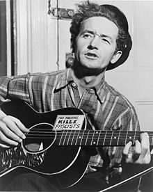 "Woodrow Wilson ""Woody"" Guthrie (July 14, 1912 – October 3, 1967) was an American singer-songwriter and folk musician whose musical legacy includes hundreds of political, traditional and children's songs, ballads and improvised works. He frequently performed with the slogan This Machine Kills Fascists displayed on his guitar. His best-known song is ""This Land Is Your Land."""