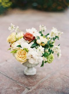 Lush floral arrangement in an antiqued white urn. #wedding #flowers #centerpiece