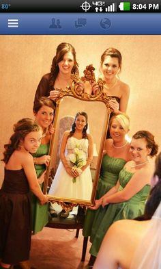 Bridesmaid holding mirror framing bride