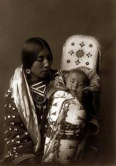 You are viewing an unusual image of an Indian Mother holding her Child. It was taken in 1908 by Edward S. Curtis.    The image shows a Portrait of a Native American woman in a half-length, seated, facing right, position holding her baby in a beaded cradleboard.    We have created this collection of images primarily to serve as an easy to access educational tool. Contact curator@old-picture.com.    Image ID# 23E39046