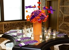 Vibrant orange and purple #centerpiece accented with small airplanes by Michael Daigian Design.