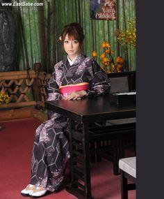 A girl wearing a black kimono cherry