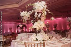 Tree like centerpieces incorporating stunning floral bouquets create a very elegant feel. Venue: Eau Palm Beach Resort & Spa in Manapalan, FL. Photo: Chris Joriann Photography
