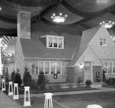 "Front entrance to model home at Home Show, Louisville, Kentucky. A couch on the front lawn bears a sign reading ""The 1931 'Model Home' furnished complete by Sears, Roebuck & Co. retail store."" 1931. :: R. G. Potter Collection"
