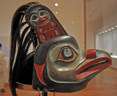 Naas shagi yeil s'aaxw (Raven at the Headwaters of Nass hat)    Tlingit, Gaanax.ádi clan, Taku.   Attributed to Kadyisdu.axch', Tlingit, Kiks.ádi clan, active late 18th – early 19th century.    Description:Ceremonial hat  Date:ca 1810; photo 2010-12-18  Medium: Maple, paint, shell, hair, baleen  Current location: Seattle Art Museum  There are human figures crouching within Raven's ears.