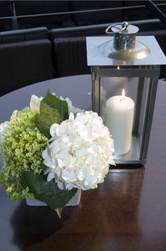 A candle in a metal lantern brightens an arrangement of white hydrangeas and beautiful greens.