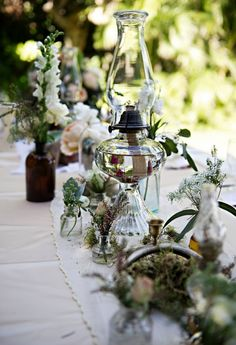 Elegant table scape with various flowers, jars and lanterns