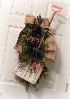 love this old child's shovel turned door decor - Use some craft wire to secure evergreen branches found in your yard.