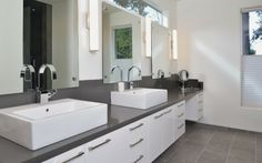 Bathroom | Dark gray bench/counter tops and floor tiles, white cabinet doors and basin. Simple and modern.