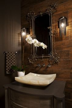 The juxtaposition of rustic wood wall and gilt ornate mirror strike an unforgettable chord.  The orchid crowns the room.