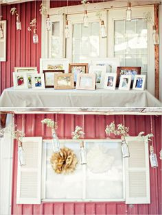 Photo display with hanging baby's breath in glass bottles. Captured By: Stephanie Sunderland Photography ---> http://www.weddingchicks.com/2014/06/03/diy-your-wedding-in-a-field/