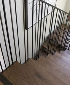 Dark wood and iron rail staircase by Medium Plenty, Remodelista