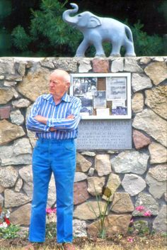 """In this 1992 photo, pharmacist Wade Meloan (now deceased) poses at the elaborate gravestone for Norma Jean, a circus elephant tragically killed 40 Julys ago in the Mississippi River town of Oquawka. Meloan, a pharmacist who spearheaded the effort to build the memorial, liked to say, """"If you can't go through life helping people, even if it's only a dead elephant, then there's no use in you being here."""""""