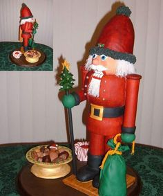 Red gingerbread dough painted with red food coloring was used for the look of stained wood in this Nutcracker created by Barbara A. of Florham Park, NJ. The nuts in the bowl, the green bag, head and votive candle were made from molded Rice Krispie treats covered with fondant. The hair is thin rice vermicelli. A Dremel, level, rulers, drill, sanding block, and paint brushes were used to build the Santa nutcracker. | thisoldhouse.com