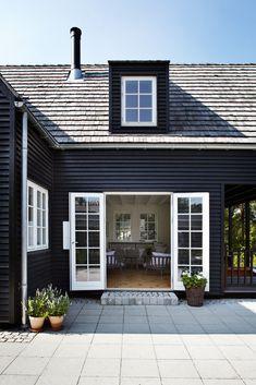 exterior: black claps + white trim + patio