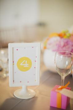 Ikea Tolsby frames for table numbers at bright and colorful pink, orange, yellow and gray weddding at Burlington Golf and Country Club | Planning and Design by www.kjandco.ca | Photography by Elizabeth In Love Read more - http://www.stylemepretty.com/2013/09/04/burlington-ontario-wedding-from-kj-co-beth-ty-in-love/