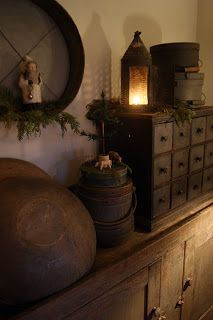 ANTIQUE DRAWERS, DOUGH BOWLS, PANTRY BOXES, LANTERN, AND FIRKINS LINE THE TOP OF A SIDEBOARD WITH AN ANTIQUE ROUND SIFTER AND SANTA HANGING ABOVE.