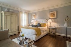 This bedroom's decor is a work of art. The contrasting gray and yellow color scheme work harmoniously. The vintage wardrobe and pillow headboard are exceptional. Lake Forest, IL Coldwell Banker Residential Brokerage