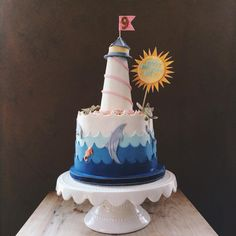 """Ocean themed 9th Birthday cake - Vanilla cake with vanilla SMBC.   Modeling chocolate waves.   Gum paste sea creatures, shells, sun.   Rice cereal treat lighthouse covered in modeling chocolate.     Graham cracker """"sand"""""""