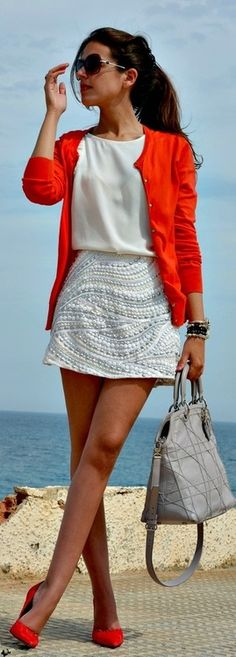 red cardigan over a white top, belt, and skirt