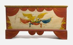 """DECORATED PINE BLANKET CHEST  19th c. pine six-board blanket chest with 20th c. decoration, rectangular top with breadboard edges, above case with interior till, raised on modified bracket feet with abbreviated swag apron, in red paint with yellow trim, the front with a spread-winged eagle clutching crossed red and blue flags on a white background, leather side handles, from a Nantucket estate, 22"""" h, 41 1/2"""" w, 17"""" d."""