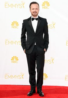 Aaron Paul rocked the Emmy's red carpet in a black kid mohair tuxedo with velvet trim, white smoking silk shirt, black bow tie and black lace-up shoes, all by Prada.