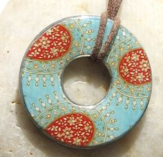 A pendant made from a washer, scrapbook paper, and mod podge.
