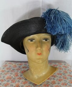 "Mid-teens fine black straw tricorne sports a dramatic froth of 2 steel blue ostrich plumes, one of which dips over the front of the hat while the other is curled into the side ""corner"". A wire-edged layer of black silk sits on top of the brim, adding textural contrast as it helps to shape the hat."