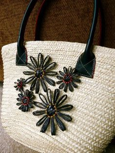 This thrift-store bag is adorned with loomed flowers made from stretched VHS tape.