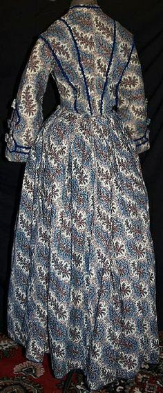 """back 1860's roller printed gown. Orange, Red & Blue floral sprays on cream wool challis background. Mostly hand sewn. Piped at waist & armscyes, has original brass hooks with handmade round eyeholes. Bodice fully lined with cream linen and openings are lined with brightly printed calico. Skirt has cartridge pleating, hem edged with blue hem protector, has deep right side pocket, skirt lined with cream & brown polished cotton. Bust: 30""""; Waist: 22""""; back length of gown: 57""""."""