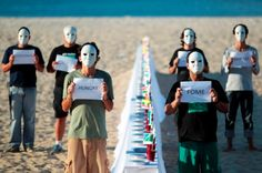 Volunteers in masks hold signs next to a table with empty plates and flags representing the problem of hunger in those countries at a protest ahead of the Rio+20 conference in Rio de Janeiro, June 19, 2012. REUTERS/Ueslei Marcelino