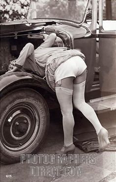 French 1920s saucy postcard with a girl posing as an unusual car mechanic stock photo