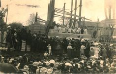 In 1911, a large crowd gathers on the lawn at St. Peters to watch laying of the cornerstone at the church. The cornerstone is visible resting on a row of large stone blocks. A group of men and boys in liturgical clothing stand next to the cornerstone. Overhead, the beginnings of the structure are taking shape.