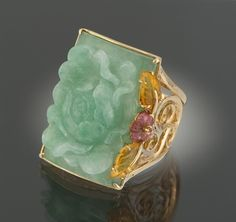 A Carved Jadeite Ring and Citrine Ring. 14k yellow gold ring with open scroll design shoulders, featuring a carved jadeite plaque depicting a chrysanthemum flower, 26 mm x 20 mm, and accented on the border with carved citrine leaves and carved amethyst flower. Overall weight 14.4 gm.